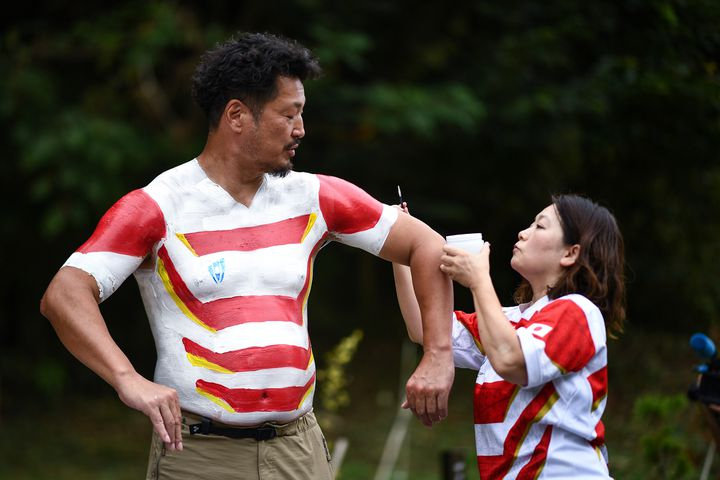 Hiroshi Moriyama se fait peindreaux couleurs du Japon, pour laCoupe du monde de rugby, le 28 septembre 2019 àShizuoka. (ANNE-CHRISTINE POUJOULAT / AFP)