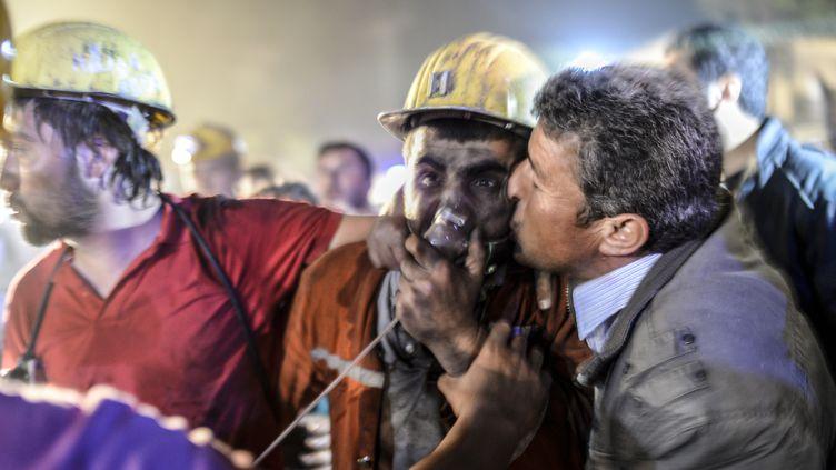 Un homme embrasse son fils, mineur à Soma (Turquie), après l'explosion due à un problème électrique. (BULENT KILIC / AFP)