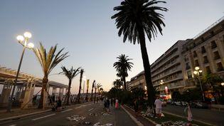 Des fleurs, des bougies et des messages laissés en hommage aux victimes de l'attentat de Nice, sur la promenade des Anglais, le 18 juillet 2016. (VALERY HACHE / AFP)