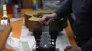 Un employé de l'entreprise Furch en train de travailler sur une guitare, en mars 2020. (MICHAL CIZEK / AFP)