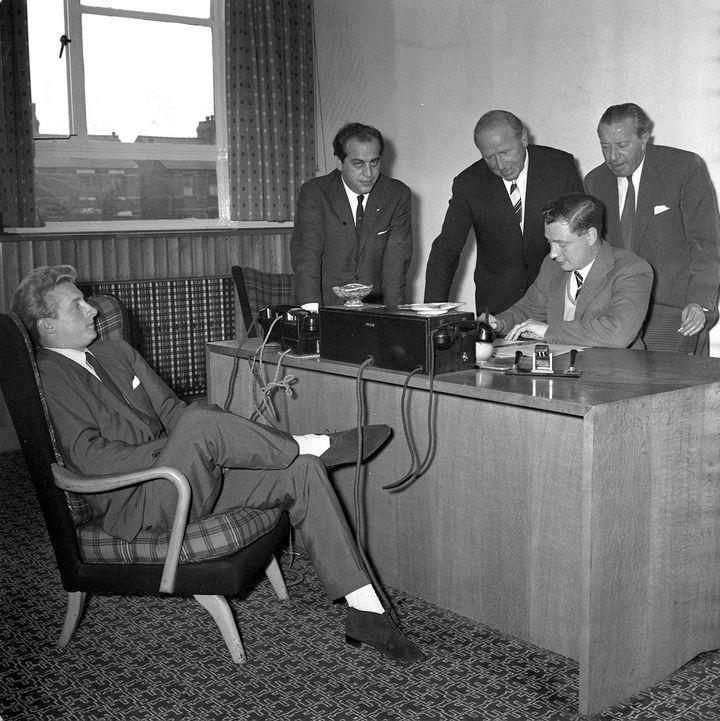 Les contrats des joueurs de foot dans les années 1960 (ici, Denis Law dans les bureaux de Manchester United en 1962) encadraient strictement les salaires et les primes des joueurs. (POPPERFOTO / GETTY IMAGES)