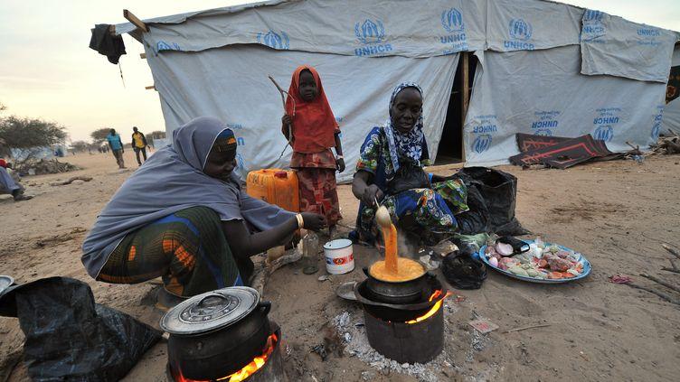 Des Nigérianes cuisinent dans un camp de réfugiés sur les rives du lac Tchad, le 26 janvier 2015. (SIA KAMBOU / AFP)