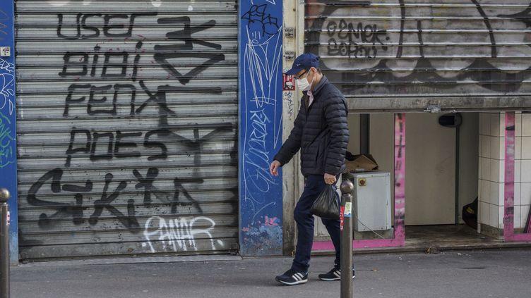 Un hommepasse devant des magasins fermés à cause de l'épidémie de coronavirus, à Paris, le 15 mars 2020. (HERVE LEQUEUX / HANS LUCAS / AFP)