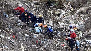 Des gendarmes poursuivent leurs investigations sur le lieu du crash de l'A320 de Germanwings, dans les Alpes-de-Haute-Provence, le 26 mars 2015. (ANNE-CHRISTINE POUJOULAT / AFP)