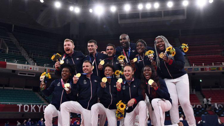 L'équipe de France mixte par équipes au comble du bonheur après avoir reçu la médaille d'or à Tokyo le 31 juillet 2021. (FRANCK FIFE / AFP)