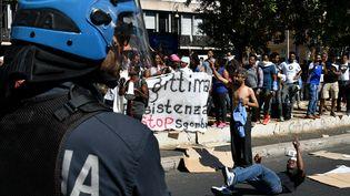 Réfugiés et demandeurs d'asile font face à la police à Rom, mercredi23 août. (ALBERTO PIZZOLI / AFP)