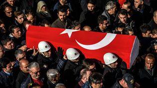Des policiers portent le cercueil d'un policier tué à Istanbul (Turquie), le 11 décembre 2016. (OZAN KOSE / AFP)