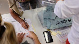 Un homme vote dans un bureau de vote lors du référendum sur l'indépendance de la Nouvelle-Calédonie, à Nouméa, le 4 octobre 2020. (THEO ROUBY / AFP)