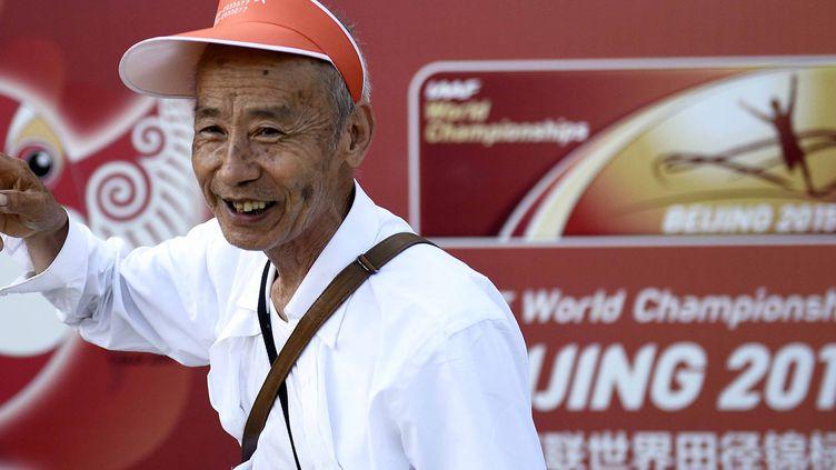 """Un homme salue la presse dans le stade """"Nid d'oiseau"""" à Pékin, 20 août 2015 (FRANCK FIFE / AFP)"""