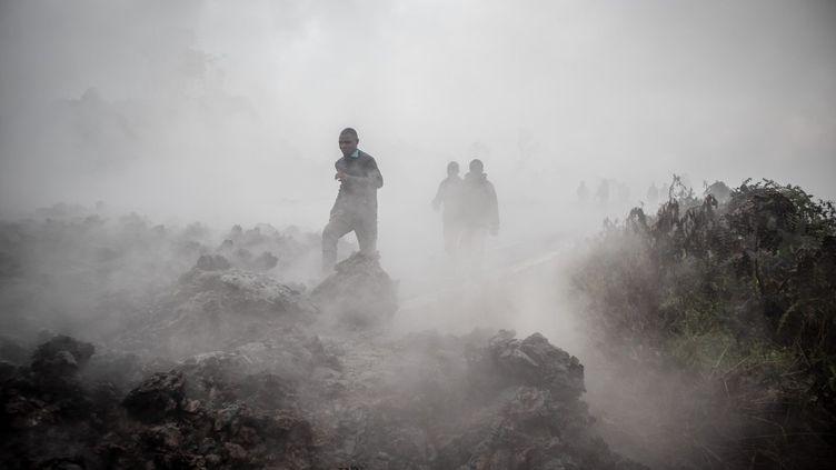 Des hommes traversent le front des roches de lave encore fumantes après l'éruption du Nyiragongo le 23 mai 2021 à Goma, dans l'est de la République démocratique du Congo. (GUERCHOM NDEBO / AFP)