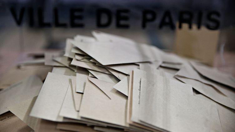 Des enveloppes dans l'urne d'un bureau de vote, à Paris, le 7 mai 2017. (ALEXANDROS MICHAILIDIS / SOOC / AFP)