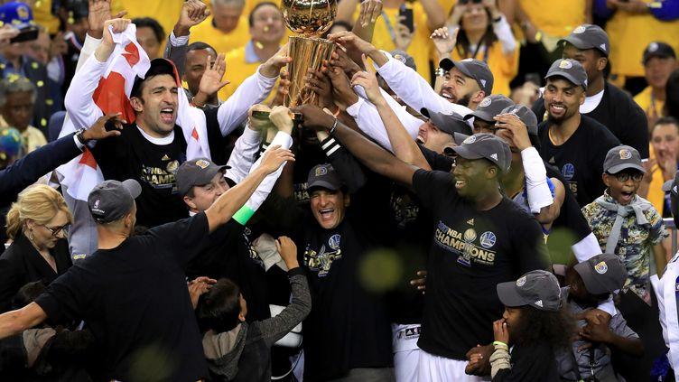 Les joueurs de Golden State soulèvent le trophée Larry O'Brien  (RONALD MARTINEZ / GETTY IMAGES NORTH AMERICA)
