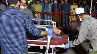 Un jeune homme blessé lors des explosions près de l'aéroport de Kaboul (Afghanistan) est pris en charge par les secours le 26 août 2021. (WAKIL KOHSAR / AFP)