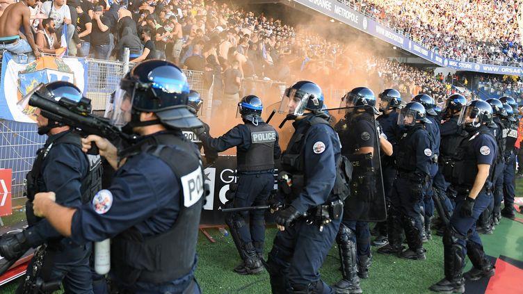 Des policiers tentent de prévenir l'envahissement du terrain lors de la rencontre Nîmes-Montepllier, dimanche 30 septembre. Un peu plus tôt, un grillage entourarant la pelouse s'était effondré. (PASCAL GUYOT / AFP)