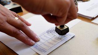 Un assesseur tamponne une carte d'électeur, à Authon (Loir-et-Cher), lors du second tour des élections législatives, le 18 juin 2017. (GUILLAUME SOUVANT / AFP)