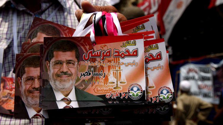 Un supporter du candidat des Frères musulmans Mohammed Morsi vend des images de son favori, place tahrir, au Caire, le 23 juin 2012. (MARWAN NAAMANI / AFP)