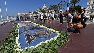 Des roses sont déposées en hommage aux victimes de l'attentat de Nice (Alpes-Maritimes), le 14 juillet 2017. (YANN COATSALIOU / AFP)