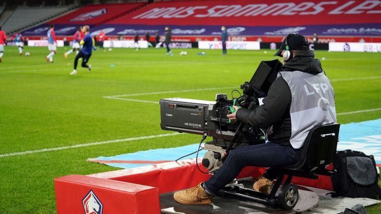 Un caméraman filme un échauffement avant le match Lille-Reims, le 17 janvier 2021, à Villeneuve-d'Ascq (Nord). (SYLVAIN LEFEVRE / HANS LUCAS / AFP)