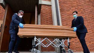 Des porteurs apportent le cercueil d'une personne décédée pour l'entreposer dans l'église de San Giuseppe à Seriate, près de Bergame, en Lombardie (Italie), le 26 mars 2020. (PIERO CRUCIATTI / AFP)