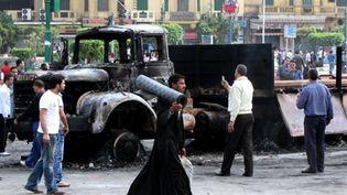 Des Egyptiens contemplent un camion incendié sur la place Tahrir, au Caire, le samedi 9 avril 2011 (AFP / Khaled Desouki)