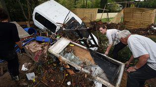 Des habitants de Lodève (Hérault) nettoient les débris laissés par les inondations, le 13 septembre 2015. (PASCAL GUYOT / AFP)