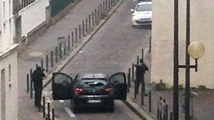 """Deux hommes armés montent à bord d'un véhicule après l'attaque menée dans les locaux de """"Charlie Hebdo"""", à Paris, le 7 janvier 2015. (ANNE GELBARD / AFP)"""