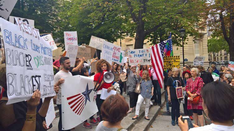 Une petite centaine de manifestants, des expatriés américains pour la plupart, ont exprimé leur mécontentement contre la politique de Donald Trump, jeudi 13 juillet 2017, place des Etats-Unis à Paris. (F. MAGNENOU / FRANCEINFO)