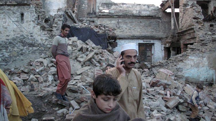 Des habitants de Mingora (Pakistan) sur les ruines de leur habitation, après le puissant séisme qui a frappé l'Asie du Sud, le 26 octobre 2015. (HAZRAT BACHA / REUTERS )