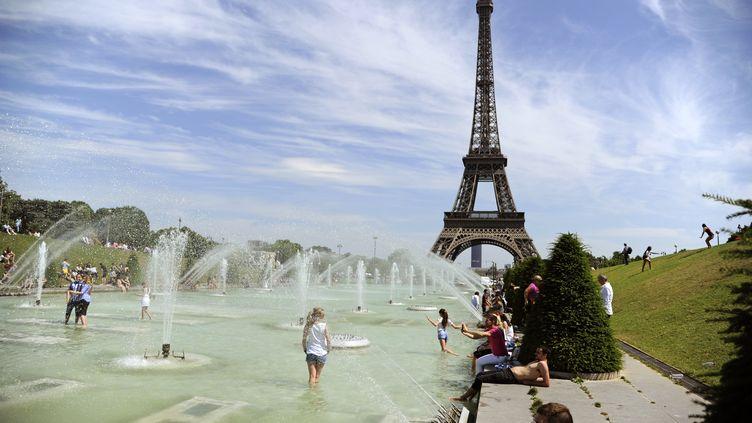 Des gens se rafraîchissent près de la Tour Eiffel, à Paris, le 26 juin 2015. (THOMAS OLIVA / AFP)
