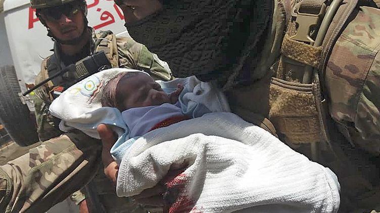 Un membre des services de sécurité afghan prend en charge un bébé après l'attaque d'une maternité à Kaboul, le 12 mai 2020. (AFP)