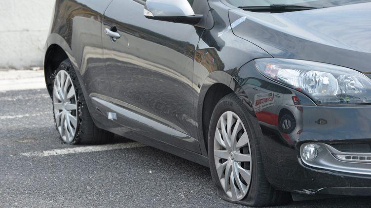 Une voiture avec les deux pneus crevés, le 25 mars 2016. (MAXPPP)