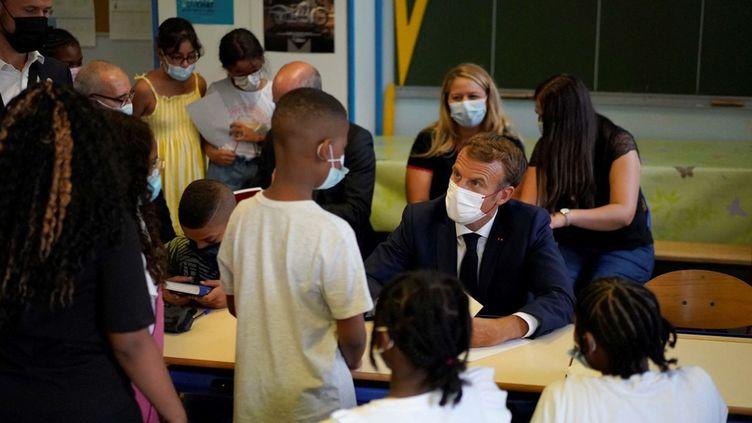 Emmanuel Macron échange avec un élève lors d'une visite dans une école à Marseille, le 2 septembre 2021. (DANIEL COLE / AFP)