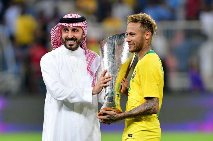 Le footballeur brésilien Neymar reçoit un trophée des mains du princeAbdul Aziz ben TurkiAl Faisal après un succès en amical contre l'Argentine, le 16 octobre 2018, à Djeddah (Arabie Saoudite). (WALEED ALI / X06847)