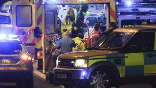 Des secouristes britanniques prennent en charge des blessés, le 3 juin 2017, à Londres, après une attaque. (DANIEL SORABJI / AFP)