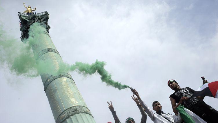 Des manifestants pro-palestinien au pied de la Colonne de Juillet, place de la Bastille à Paris, dimanche 13 juillet. (KENZO TRIBOUILLARD / AFP)