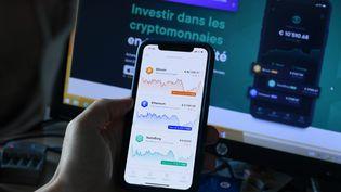 Un homme regarde les cours des cryptomonnaies, à Lyon le 25 août 2021 (illustration). (JO?L PHILIPPON / MAXPPP)
