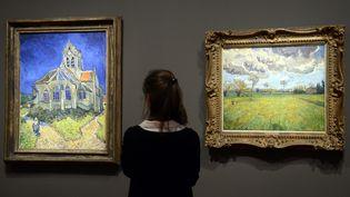 """A gauche, """"L'Eglise d'Auvers-sur-Oise vue du chevet"""". A droite, """"Paysage sous un ciel de tourmente"""". Les deux toiles figurent parmi les œuvres de Vincent Van Gogh présentées au musée d'Orsay, à partir du 11 mars 2014. (BERTRAND GUAY / AFP)"""