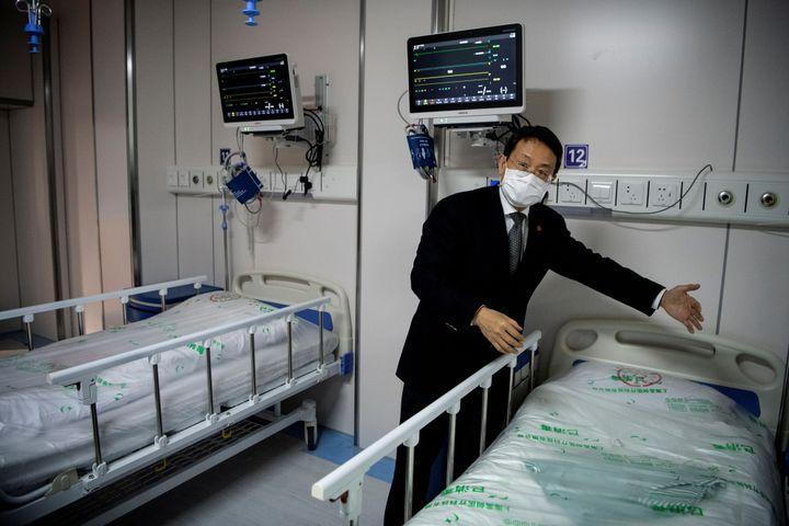 Le docteur Lu Hangzhou, professeur et codirecteur du Centre de santé publique de Shanghai, montre une salle de quarantaine pour les patients atteints de coronavirus Covid-19, le 17 février 2020, à Shanghai (Chine). (REUTERS)