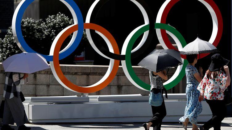 Des passants devant les anneaux olympiques, dans le quartier deNihonbashi à Tokyo (Japon), le 5 août 2019. (ISSEI KATO / REUTERS)