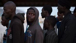 Un groupe de migrants sauvés par les gardes-côtes espagnols, dans le porte de Motril, en Andalousie (Espagne), le 23 juillet 2017. (JORGE GUERRERO / AFP)