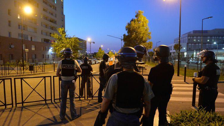 Lors des échauffourées qui ont débuté jeudi 18 juillet à Trappes (Yvelines), des tirs de mortier ont été tirés. Ici, la BAC (Brigade anti-criminalité) se déploie dans la ville le 20 juillet 2013. (MIGUEL MEDINA / AFP)