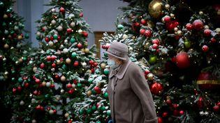 Une femme porte un masque devant des sapins de Noël, le 1er décembre 2020 à Moscou (Russie). (NATALIA KOLESNIKOVA / AFP)