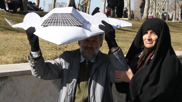 Un couple brandit une réplique miniature du drone RQ-170 américain que l'Iran dit avoir capturé, le 11 février 2012 à Téhéran. (ATTA KENARE / AFP)