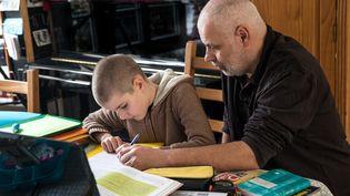 Un père aide son fils à apprendre ses leçons à la maison, pendant le confinement, à Versailles (Yvelines), le 3 avril 2020. (KARINE PERON LE OUAY / HANS LUCAS / AFP)