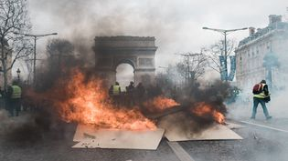 """Des manifestants mettent le feu à une barricade sur les Champs-Elysées, face à l'Arc de triomphe, lors du 18e samedi de mobilisation des """"gilets jaunes"""", le 16 mars 2019. (KARINE PIERRE / HANS LUCAS / AFP)"""