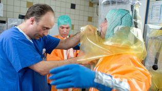 Des scientifiques allemands se livrent à un exercice de simulation pour se préparer à une éventuelle épidémie d'Ebola, le 5 août 2014 à Francfort. (BORIS ROESSLER / DPA / AFP)