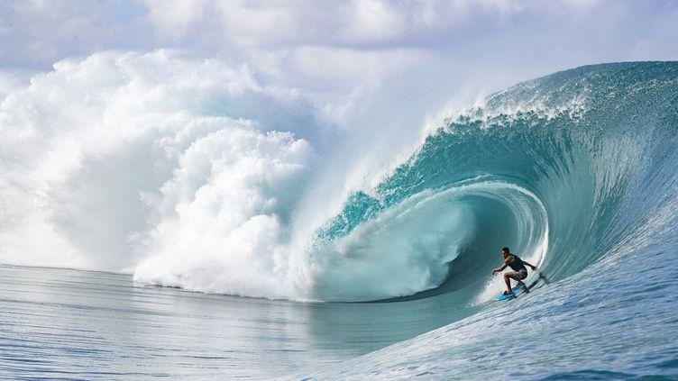 Un surfeur sur la vague mythique Teahupoo, à Tahiti, le 8 août 2019. (BRIAN BIELMANN / AFP)
