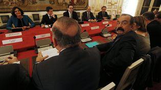 La ministre du Travail, Myriam El Kohmri, aux côtés du Premier ministre Manuel Valls face aux représentants des syndicats, notamment Philippe Martinez, secrétaire général de la CGT (au premier plan, tourné vers l'objectif), le 20 novembre 2015, à Matignon (Paris). (THOMAS SAMSON / AFP)