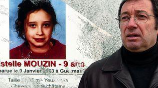Eric Mouzin, à côté de l'avis de recherche avec la photo de sa fille, en 2003, à Guermantes (Seine-et-Marne). (MAXPPP / JESSICA KOMGUEN)