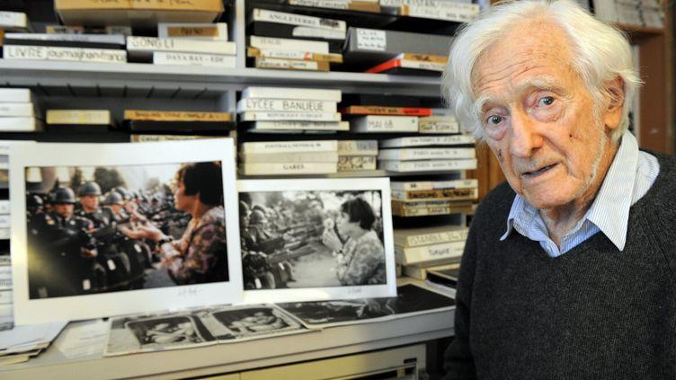 Le photographe Marc Riboud pose avec deux de ses clichés les plus célèbres, dans sa maison de Nancy (Meurthe-et-Moselle), le 9 décembre 2011. (MAXPPP)